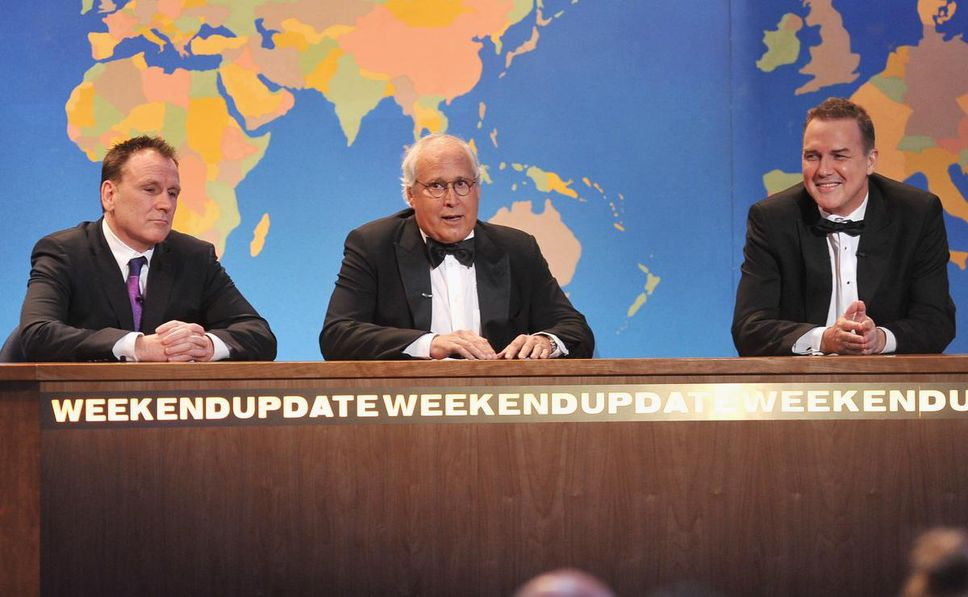 """One of his most popular roles in """"SNL"""" he was hosting the Weekend Update, a satirical version of the weekly news.  He appears here on the set of SNL in a 2012 segment of The Comedy Awards with Colin Quinn and Chevy Chase."""
